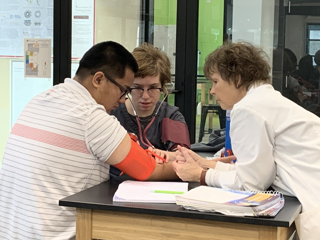 Debbie Kennedy watches as students practice measuring blood pressure.