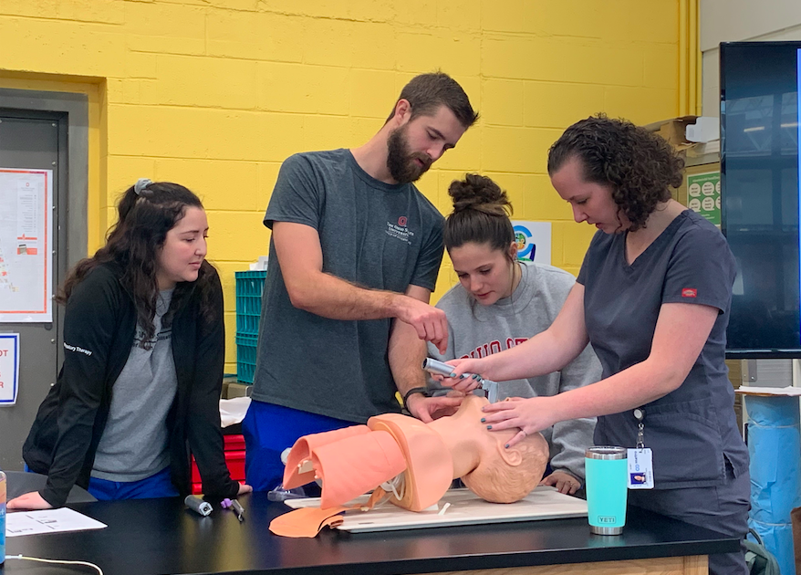 Evan and Taylor assist a student learning how to preform a tracheal intubation.