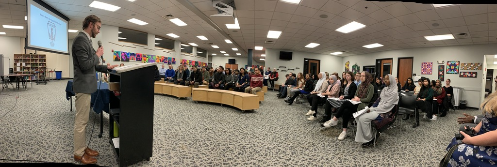 Panoramic image of speaker, parents and inductees.